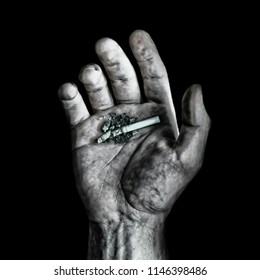 hand of man smoking cigarette with ashtray full of cigarette ends and ash in disgusting unhealthy addiction and bad habit calling for quitting tobacco addiction and keeping a healthy lifestyle