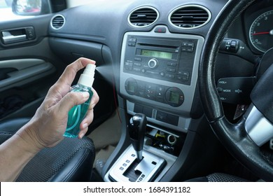 Hand of man is spraying alcohol,disinfectant spray on steering wheel in his car,prevent infection of Covid-19 virus,contamination of germs or bacteria,wipe clean surfaces that are frequently touched