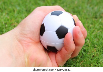 Hand of man squeezing a small black and white stress ball on green grass background