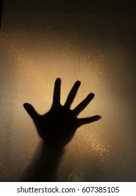 hand of a man with stretched finger against opaque and obscure glass