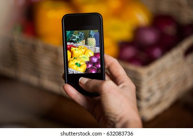 Hand of man taking photo of vegetables in market