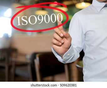 Hand of man touching text ISO9000 with white color on blur interior background,concept of adoption to promote your business for organization.