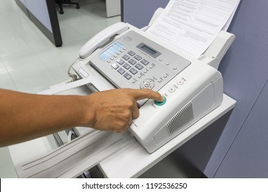 Hand man are using a fax machine in the office. Business concept
