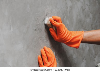 Hand of man wearing orange rubber gloves is used to convert scrub cleaning on the concrete wall.