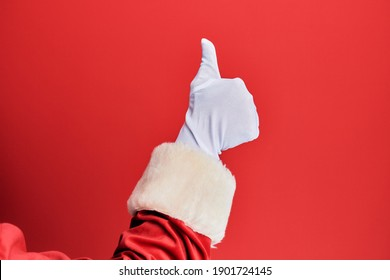 Hand of a man wearing santa claus costume and gloves over red background doing successful approval gesture with thumbs up, validation and positive symbol