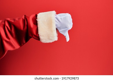 Hand of a man wearing santa claus costume and gloves over red background doing thumbs down rejection gesture, disapproval dislike and negative sign