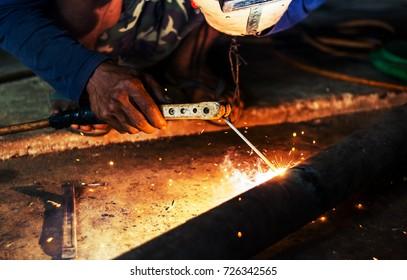 Hand of man welding steel blurred on black background, Welder concept filter color style