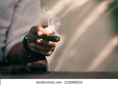 Hand of a man in white basic shirt sitting in the shadow and smoking cigar.Man spent his time with a good cigar.Blurred image of small gun at foreground.Concept of mafia or god's father or big guy.