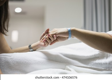 hand of man and woman couple in hospital and patient bed with hospital tag on wrist with love hope and care