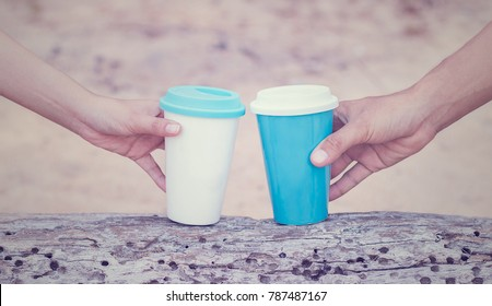 Hand of man and woman holding cups on old wooden background in the beach.