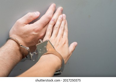 Hand of a man and a woman in metal handcuffs close-up. Codependency concept