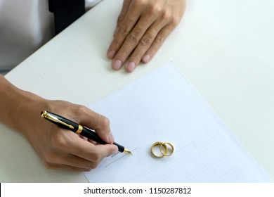 Hand man woman on paper with marry ring on paper to sign marriage or divorce