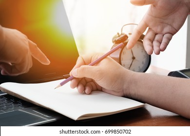 Hand of a man writing on blank paper with a pencil and other man hand pointing on his work. Busy working concept.