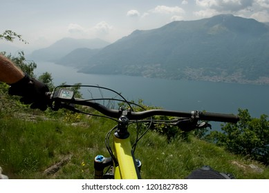 hand of man with yellow electric bicycle, e-bike, ebike, mountain, valley, lake of Como, summer, sport, adventure, sun, alps, Italy