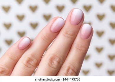Hand with manicure at the creative background with hearts. Ombre gradient nail design.