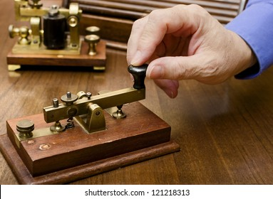 A hand manipulating an old morse transmitter