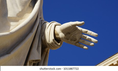 hand of a marble statue of a philosopher taken from below