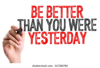 Hand with marker writing: Be Better Than You Were Yesterday
