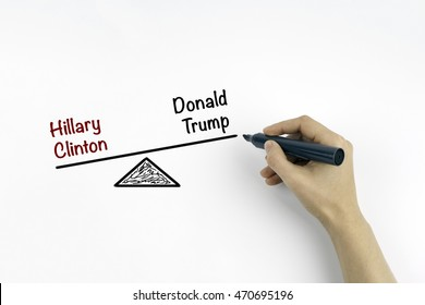 Hand with marker writing Hillary Clinton  and Donald Trump balance