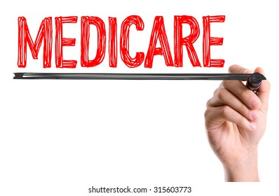 Hand with marker writing the word Medicare