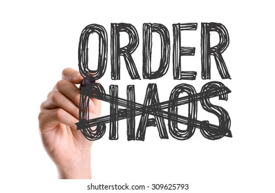 Hand with marker writing the word Order Chaos