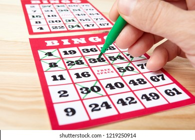 Hand marking bingo winning numbers.
