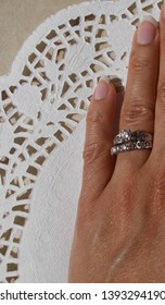 Hand of a married biracial female on white and tan background