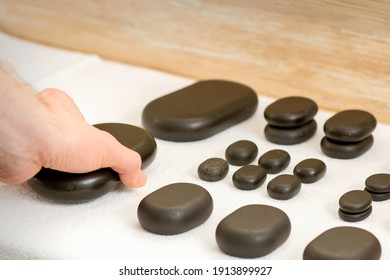 Hand of massage therapist taking massage stones from the table before massage procedures