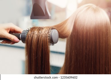Hand of master girl in beauty salon makes drying and styling with Hairdryer shiny strands dark brown hair