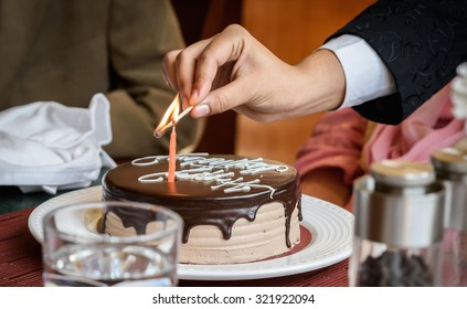 Hand with match lighting candle on birthday cake