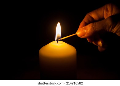 hand with matchstick, lighting a candle