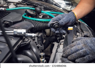 hand of Mechanic check water in car radiator and add water antifreeze coolant fluid to car radiator at garage , car maintenance and service and repair concept . selective focus