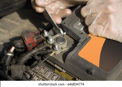 The hand of a mechanic with a flat key unscrews the battery in the car.