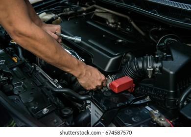 Hand of mechanic is repairing car engine