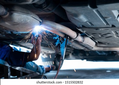 The hand of a mechanic or welder is fixing a car exhaust system by welding the exhaust pipe. Sparks of automobile exhaust pipe welding. Auto services. Selective focus. Copy space.