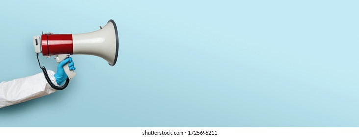 hand of medic or Nurse with gloves and a megaphone in front of an empty blue background, banner size, with copyspace for your individual text.