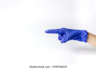 Hand in medical glove with finger pointing to the side on a white background. A place for text.