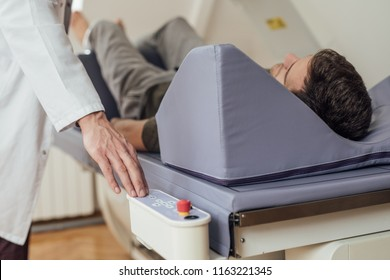 Hand of a medical technician operating the bone densitometer while his patient is lying on the bed.