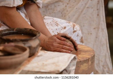 Hand of medieval craftsman female potter preparing clay - moistens and kneads the clay before work