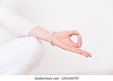 Hand meditating girl in white clothes sitting in a pose Siddhasana