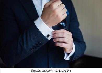 hand men wears cufflinks close up