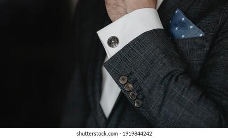 Hand men wears cufflinks close up.