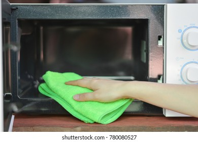 Hand with microfiber cleaning rag wiping inside of microwave oven,Cleaning the microwave oven,Hand with microfiber cleaning rag wiping inside of microwave oven
