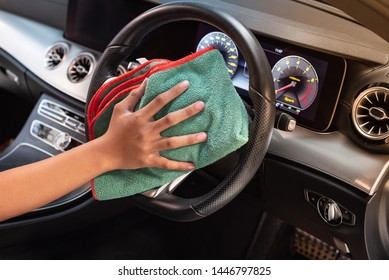 Hand with microfiber cloth cleaning car interior, Fucus  On Hand