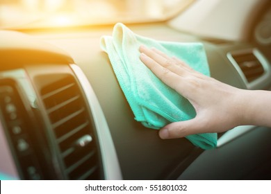 Hand with microfiber cloth cleaning leather seat,auto detailing and valeting concept,washing car care interior,selective focus,vintage co