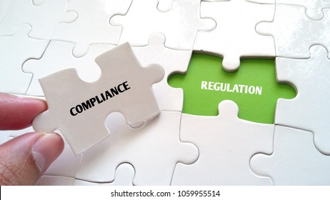 hand and missing puzzle with COMPLIANCE REGULATION WORD