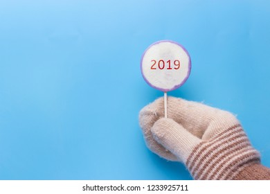 hand in mitten holding lollypop