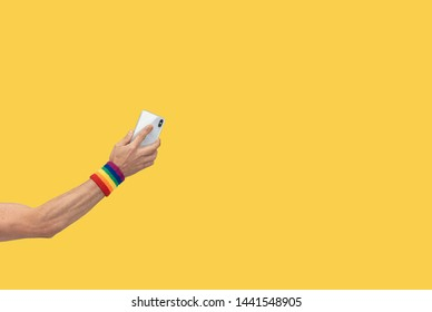 hand with mobile phone with gay pride symbol