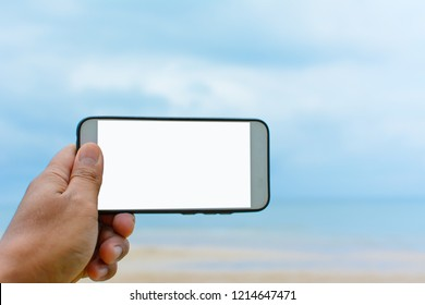 Hand with mobile smart phone over sea and sky background. Copy space for text with blank screen. Can used for selfie photo or take a photo by smartphone concepts.
