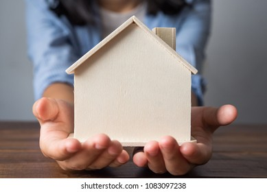 Hand with model house extended